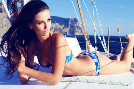 sexy photo: Fashion outdoor summer photo of sexy beautiful woman with dark long hair and slim sexy body wearing blue bikini, relaxing and posing on a yacht in the open ocean