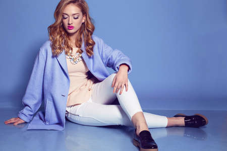 fashion studio photo of gorgeous woman with blond curly hair in spring outfit: elegant coat, blouse,pants and luxurious necklace