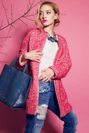 fashion studio photo of gorgeous young woman with blond curly hair wears elegant pink coat,blouse and jeans,holding a big bag in hands
