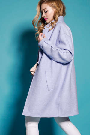 fashion studio photo of gorgeous woman with blond curly hair in spring outfit: elegant coat and white pants