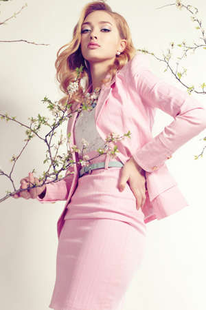 faldas: estudio de moda foto de mujer hermosa joven con el pelo rizado rubio viste elegante traje de color rosa y bijou, posando entre las ramas en flor de primavera