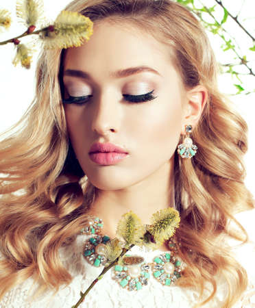 bijou: fashion studio photo of gorgeous young woman with blond curly hair wears elegant lace dress and bijou, posing among blossom willow twigs Stock Photo