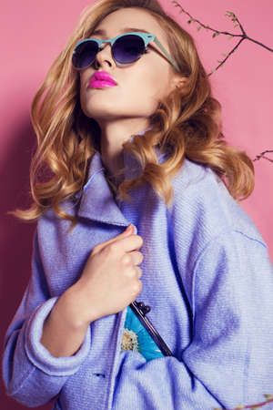 fashion studio photo of gorgeous woman with blond curly hair in spring outfit: elegant coat, suit and sunglasses, holding bag