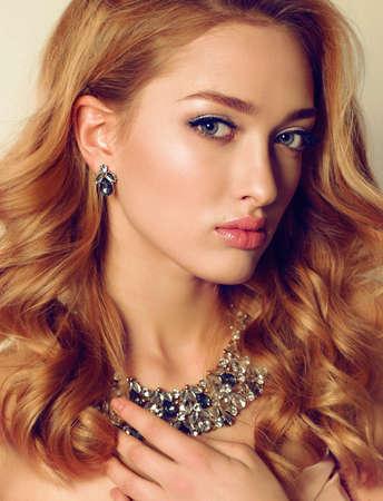 bijou: fashion studio portrait of young woman with blond curly hair wears luxurious bijou Stock Photo