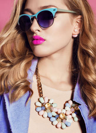 fashion studio photo of gorgeous woman with blond curly hair in spring outfit: elegant coat, dress and sunglasses