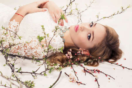 fashion studio photo of gorgeous young woman with blond curly hair wears elegant lace dress and bijou, posing among blossom twigs