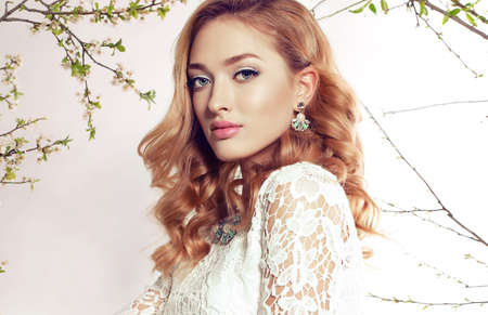 fashion studio photo of gorgeous young woman with blond curly hair wears elegant lace dress and bijou, posing among spring blossom twigs Foto de archivo