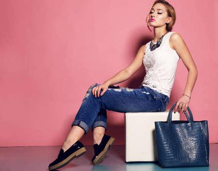 mode: mode studio foto van prachtige jonge vrouw met blond krullend haar draagt elegante blouse en spijkerbroek, met een grote zak in handen Stockfoto