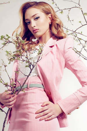 fashion studio photo of gorgeous young woman with blond curly hair wears elegant pink suit and bijou, posing among spring blossom twigs