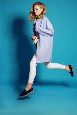fashion studio photo of gorgeous woman with blond curly hair in spring outfit: elegant coat, blouse and white pants