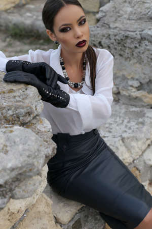 Fashion outdoor photo of sexy elegant woman with dark hair wears white shirt, black leather skirt and gloves,posing in the old town