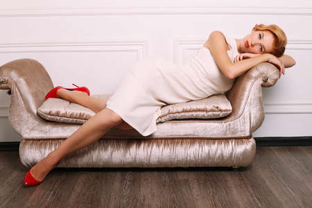 fashion studio photo of beautiful young woman with blond hair in retro style,wears elegant white dress,lying on divan