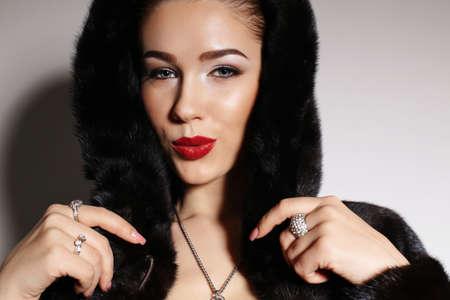 bijou: fashion studio photo of gorgeous sensual woman with elegant hairstyle,wears red dress,fur coat and bijou Stock Photo