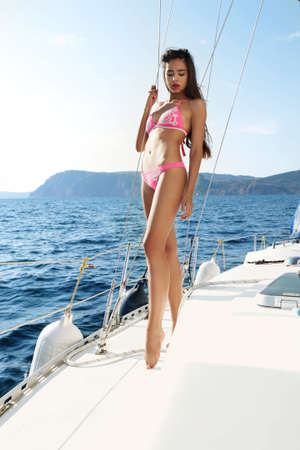 sexy black woman: Fashion outdoor summer photo of sexy beautiful woman with dark long hair and slim sexy body wears bikini, relaxing and posing on a yacht in the open ocean