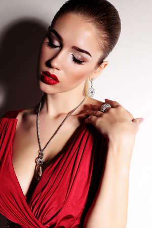 bijou: fashion studio photo of gorgeous sensual woman with elegant hairstyle,wears red dress and bijou