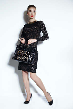 bijou: fashion studio photo of gorgeous sensual woman with elegant hairstyle,wears black dress and bijou,holding a bag