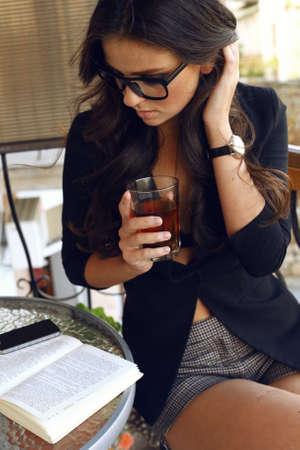 Fashion foto van mooie sexy vrouw met donker krullend haar, gekleed in zwarte jas, horloge en een bril, zittend aan cafe en het drinken van thee