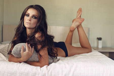 黒のランジェリーは、寝室のベッドの上でリラックスした長い黒髪の美しいセクシーな女性のファッション写真 写真素材