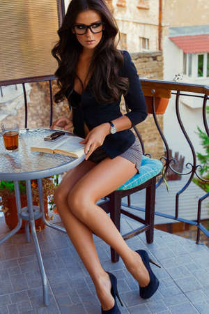 Fashion photo of beautiful sexy business woman with dark curly hair in jacket,watch, glasses,shoes,sitting with a book  in cafe,drinking tea Stok Fotoğraf