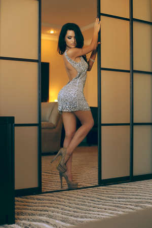 fashion interior photo of sexy beautiful girl with long dark hair wears elegant dress and accessories,posing in bedroom