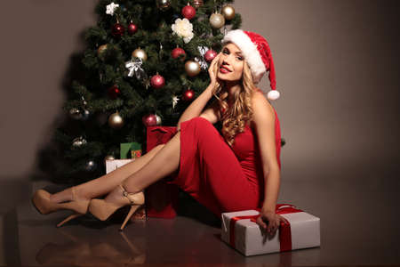 fashion studio photo of beautiful young woman with blond curly hair wears Santa hat and elegant red dress,posing with presents, beside Christmas tree