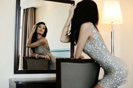 photo of accessories: fashion interior photo of sexy beautiful girl with long dark hair wears elegant dress and accessories,looking at mirror,posing in bedroom