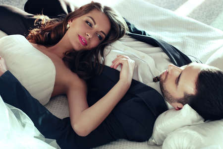 fashion interior photo of beautiful tender couple, groom and bride wear wedding clothes,embracing  in bedroom Stock Photo