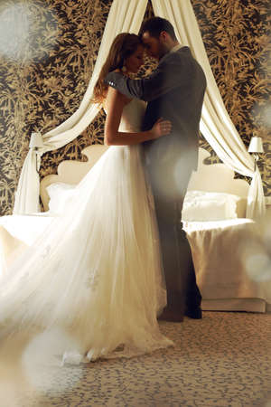 fashion interior photo of beautiful tender couple, groom and bride wear wedding clothes,embracing  in bedroom Foto de archivo