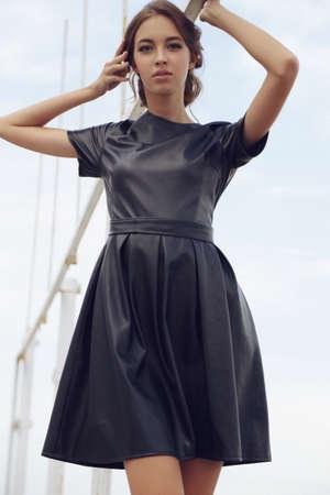 fashion photo of beautiful young girl with dark hair in elegant dress,posing outdoor Foto de archivo
