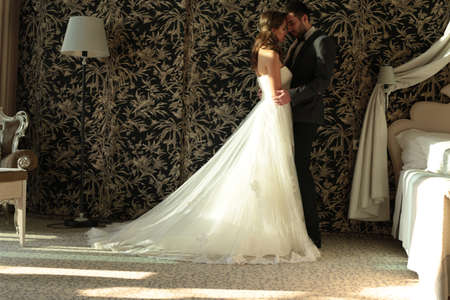 parejas sensuales: la moda entre la foto de la ropa de boda hermosa par de licitación, el novio y la novia de desgaste, en el dormitorio abrazar