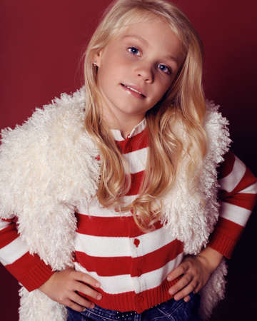 cute little girl whith long blond hair and blue beautiful eyes in fur coat,jeans skirt and striped sweater smiling and posing in the studio