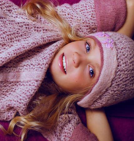 pouf: fashion studio foto of cute blond little girl  lying on purple pouf