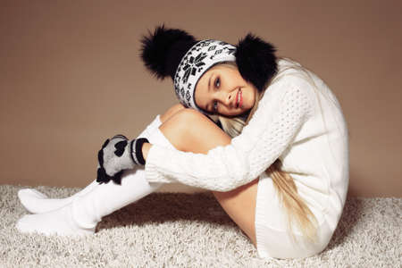 fashion studio photo of beautiful little girl with long blond hair in cozy knitted clothes posing on beige carpet