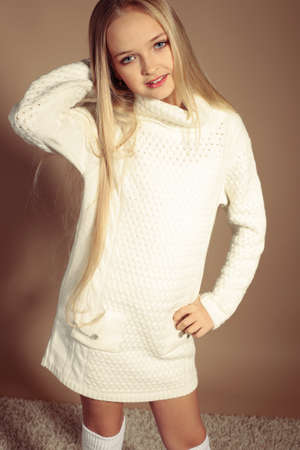 fashion studio photo of beautiful little girl with long blond hair in cozy knitted clothes Stock Photo