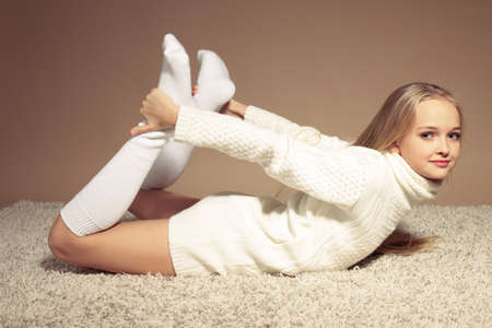 fashion studio photo of beautiful little girl with long blond hair in cozy knitted clothes lying on beige carpet