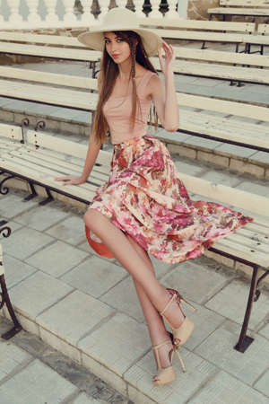 beauty girls: fashion outdoor photo of beautiful young woman with long dark hair wears elegant dress and hat,posing in summer park Stock Photo
