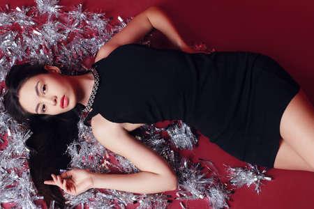 wears: fashion photo of beautiful glamour woman with long dark hair wears elegant dress with bijou, posing with Christmas decoration Stock Photo