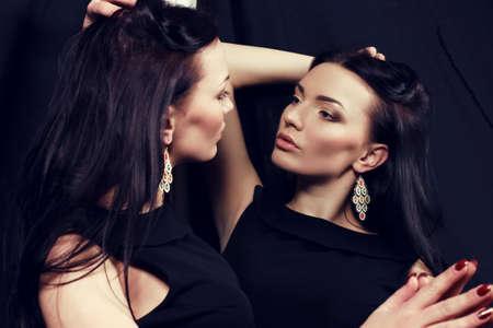 bijou: fashion studio photo of beautiful woman with dark hair in elegant dress and bijou, posing beside mirror Stock Photo