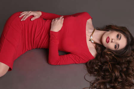 glamour hair: fashion studio photo of beautiful woman with dark curly hair wears elegant red dress and bijou