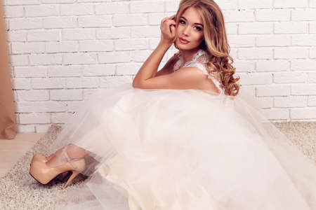 fashion studio photo of gorgeous young bride with blond curly hair, wears elegant lace wedding dress and crown on head, sitting on beige carpet