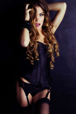 Beautiful woman in lingerie corset and pantyhose, posing on a black wall and holding her luxurious long curly hair