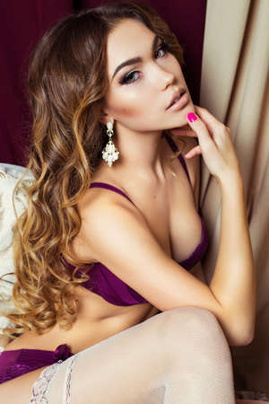 fashion interior photo of gorgeous tanned  woman with long dark curly hair and bright makeup,wears lingerie and pantyhose Stock Photo