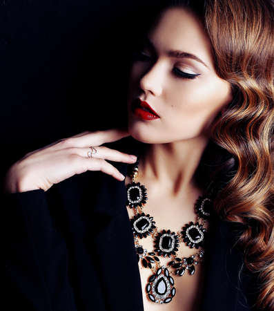 fashion studio photo of beautiful woman with dark curly hair, wears elegant clothes and bijou necklace Stok Fotoğraf