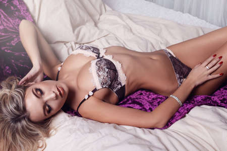 chic woman: fashion photo of beautiful young woman with long blond curly hair in elegant lingerie,posing at bedroom
