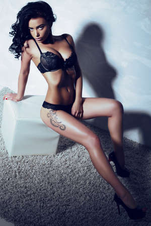 fashion studio photo of sexy gorgeous woman with dark hair and tanned body, wears elegant lingerie