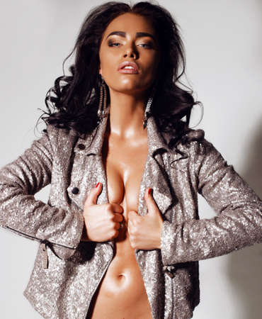sexy nude women: fashion interior photo of gorgeous tanned  woman with long dark curly hair and bright makeup,wears lingerie and jacket