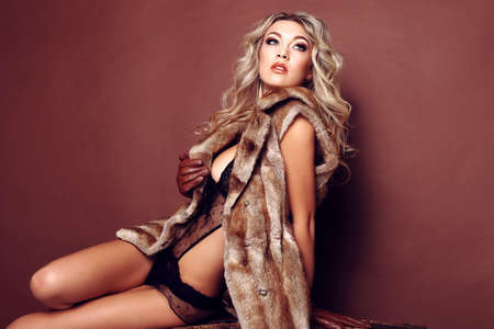 fashion photo of beautiful young woman with long blond curly hair in elegant lingerie and fur coat