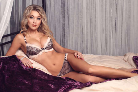 fashion photo of beautiful young woman with long blond curly hair in elegant lingerie,posing at bedroom