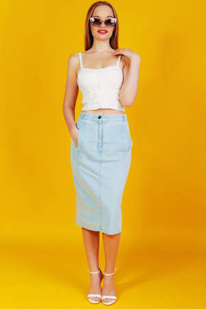 denim skirt: fashion look of elegante blond woman with beautifull long hair in stylish sunglasses, white top, denim skirt and hight heels sandals posing at studio