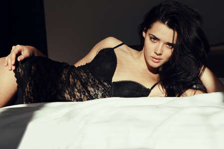 fashion photo of glamour beautiful woman with dark hair in lace lingerie dress lying in bed in the morning